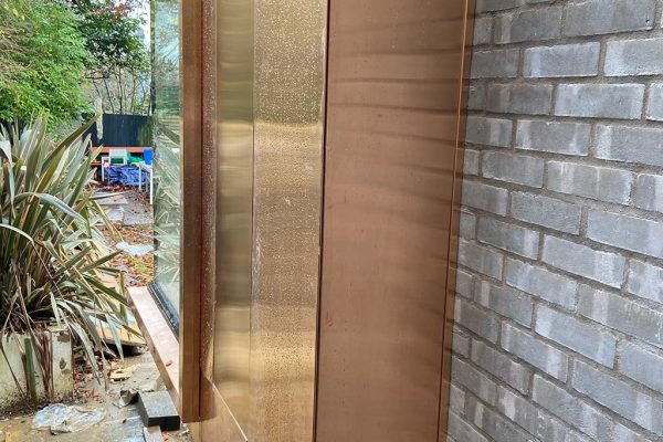 Bronze-cladding--with-secret-opening-panel